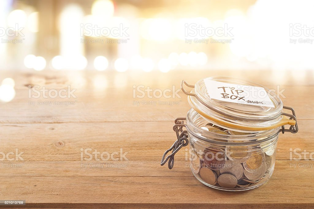 Tip box, coin in the glass jar in cafe front stock photo
