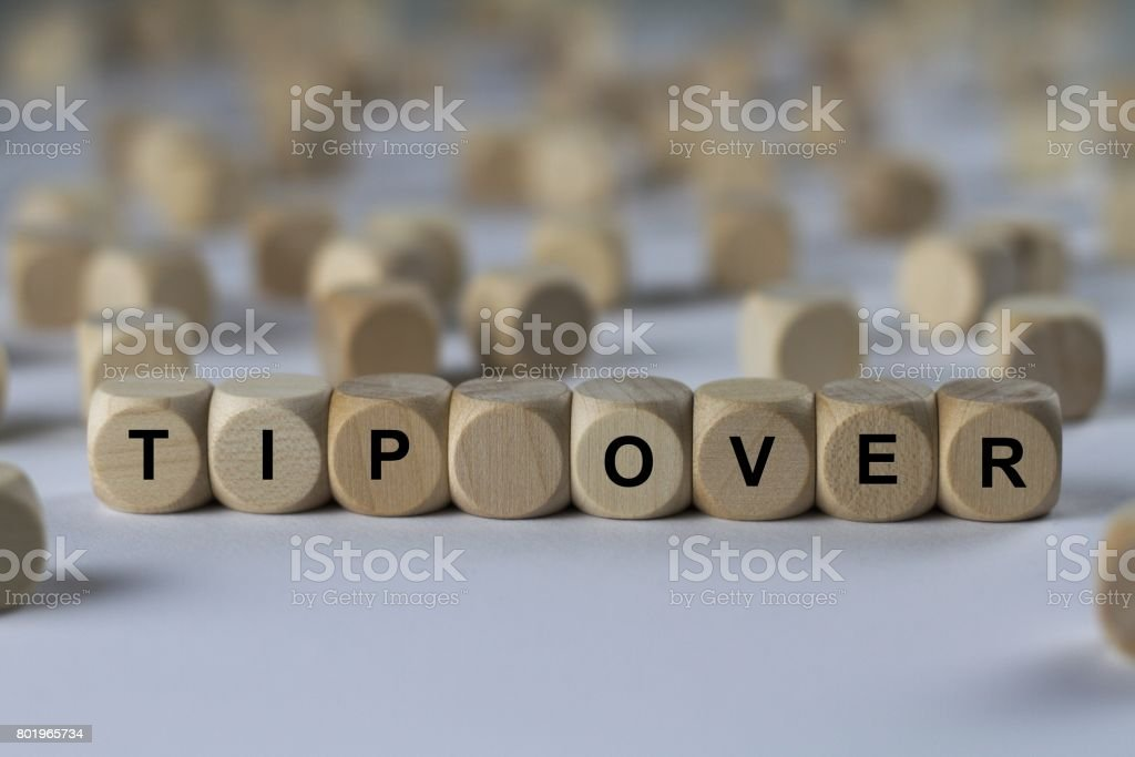 tip over - cube with letters, sign with wooden cubes stock photo