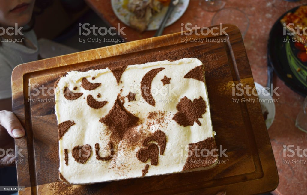 tiramisu decorated with drawings stencil of cocoa on a dark wooden Board stock photo