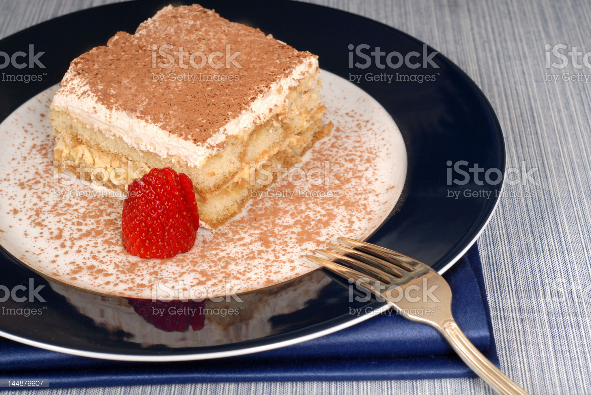 Tiramisu dusted with cocoa on a blue plate royalty-free stock photo