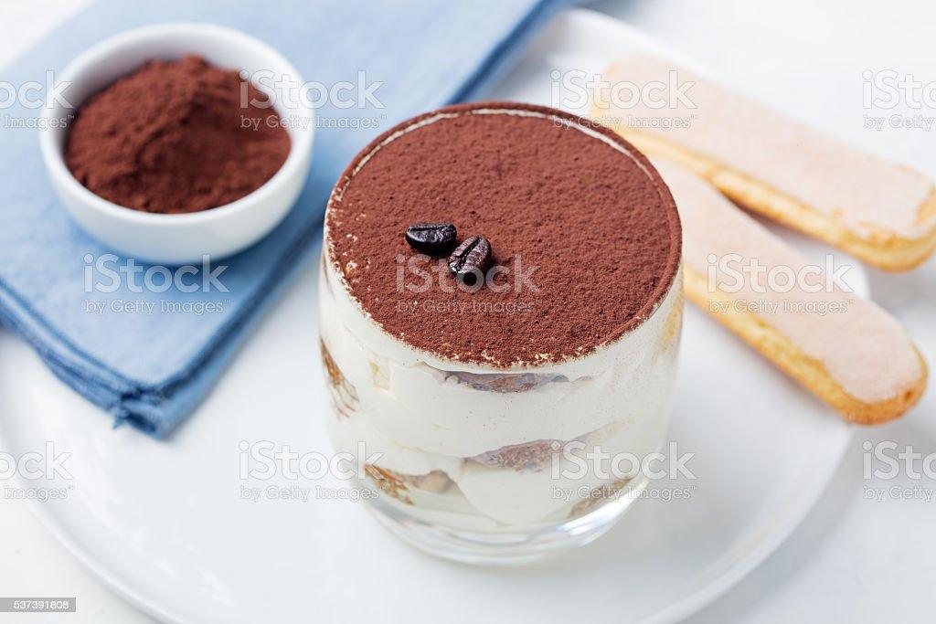 Tiramisu, traditional Italian dessert in glass on grey stone background stock photo