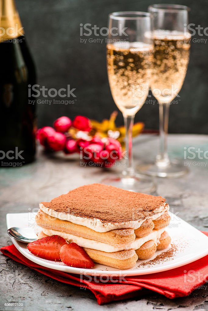 Tiramisu with strawberry and glasses of champagne on the table stock photo