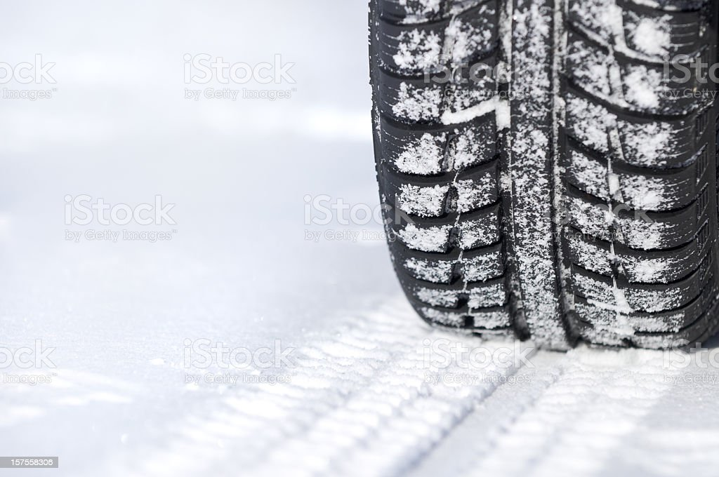 A tire leaving tracks in the snow stock photo