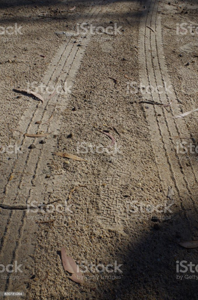 Tire marks on unpaved road stock photo