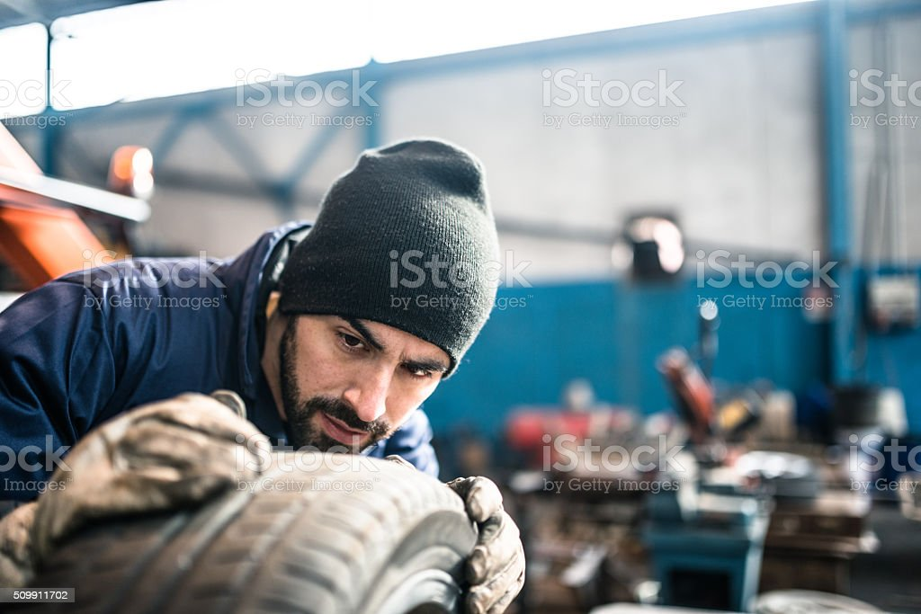 tire repairer checking the tire integrity stock photo