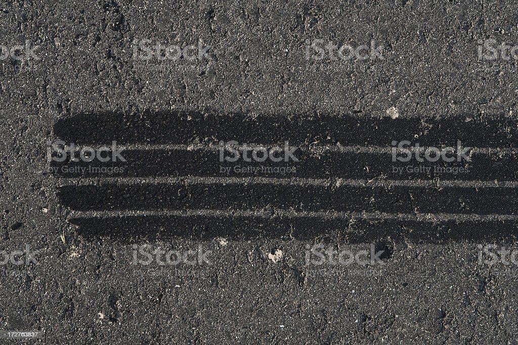 Tire track on weathered asphalt stock photo