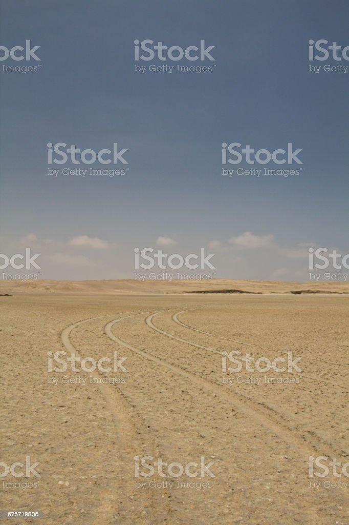 Tire tracks in sand. Perfect place to see tropical desert, wide cliffs and coloful beaches on the rocky islands and national reserve. Small islands near the town of Paracas. stock photo