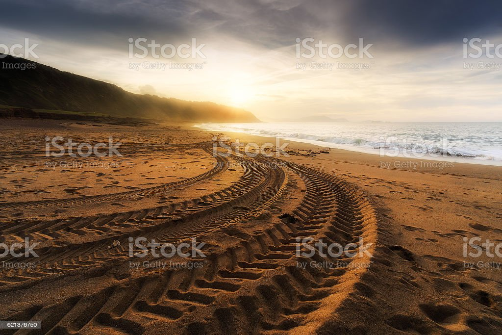 tire tracks prints in beach sand stock photo