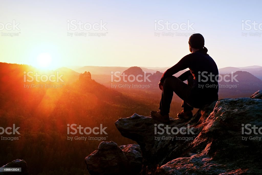 Tired adult hiker in black trousers, jacket, cap on cliff stock photo