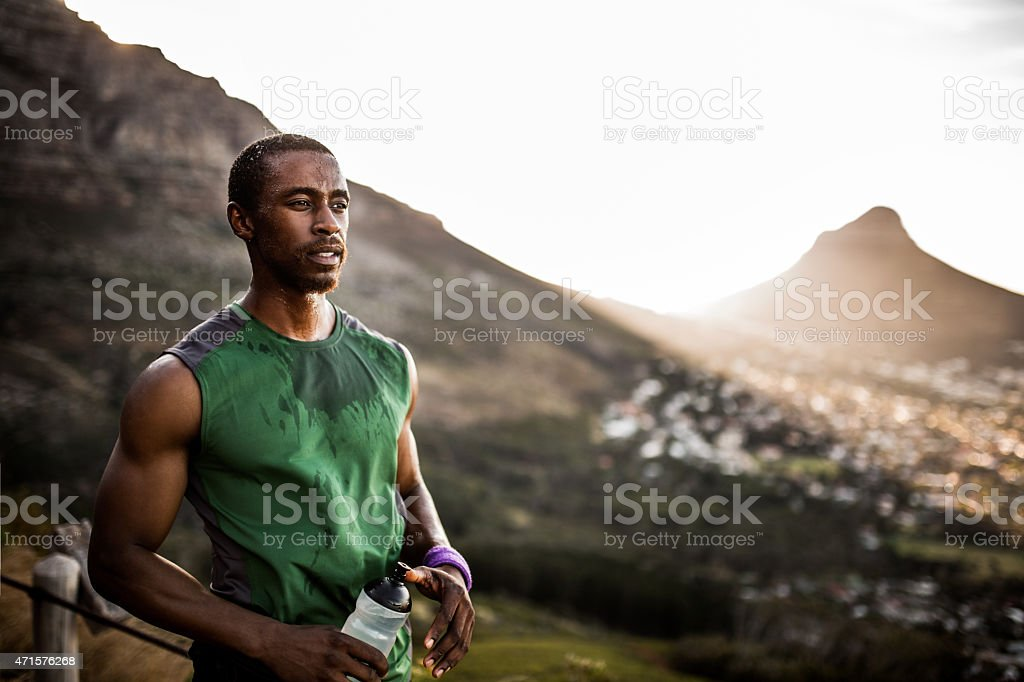 Tired African American athlete looking positively after serious stock photo