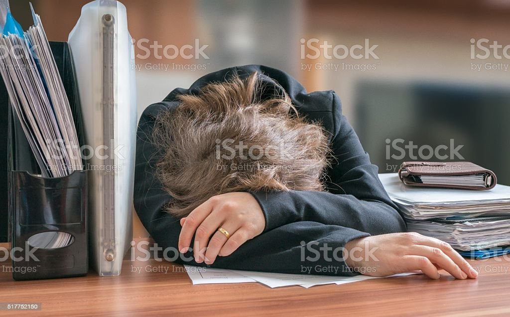 Tired and exhausted workaholic woman sleeping on desk in office. stock photo