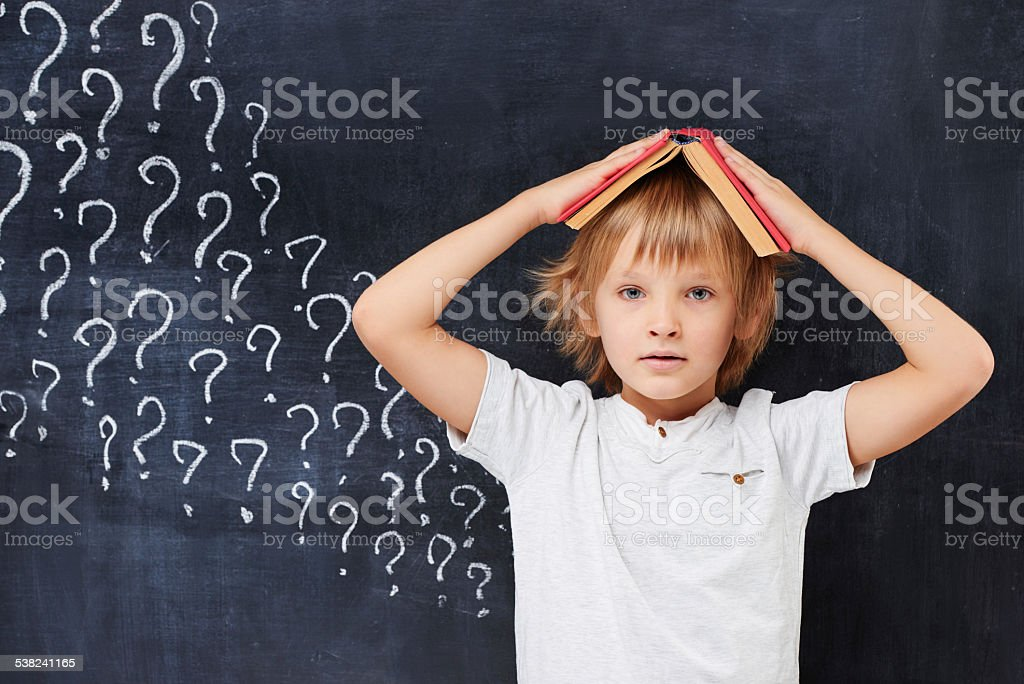 Tired and mixed-up primary school age boy  with ginfer hair stock photo