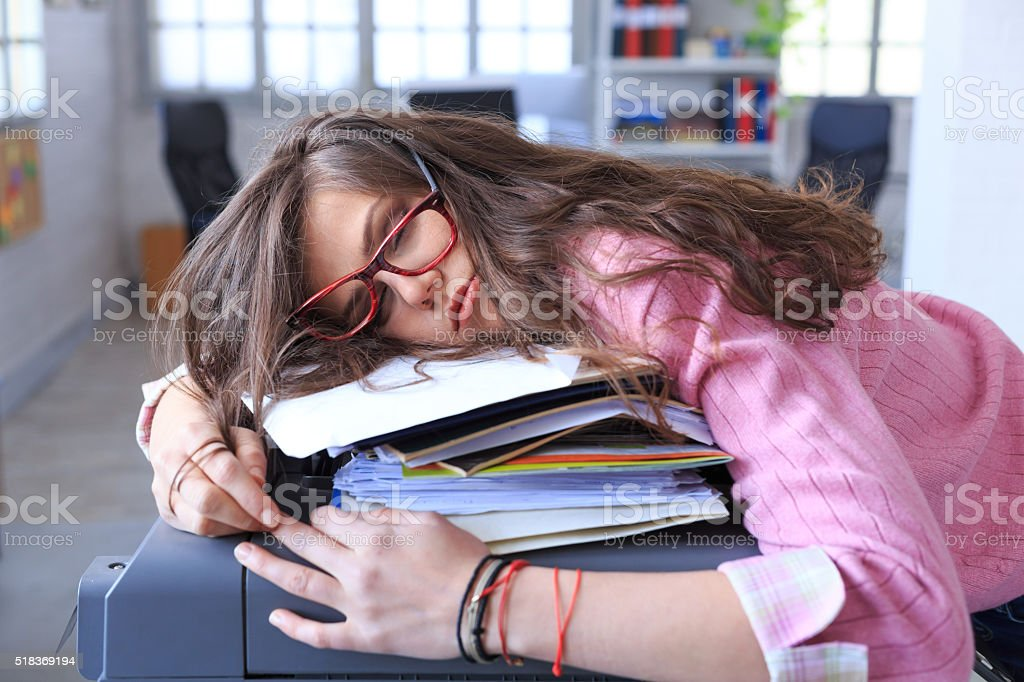 Tired assistant sleeping on a copy machine at the office stock photo
