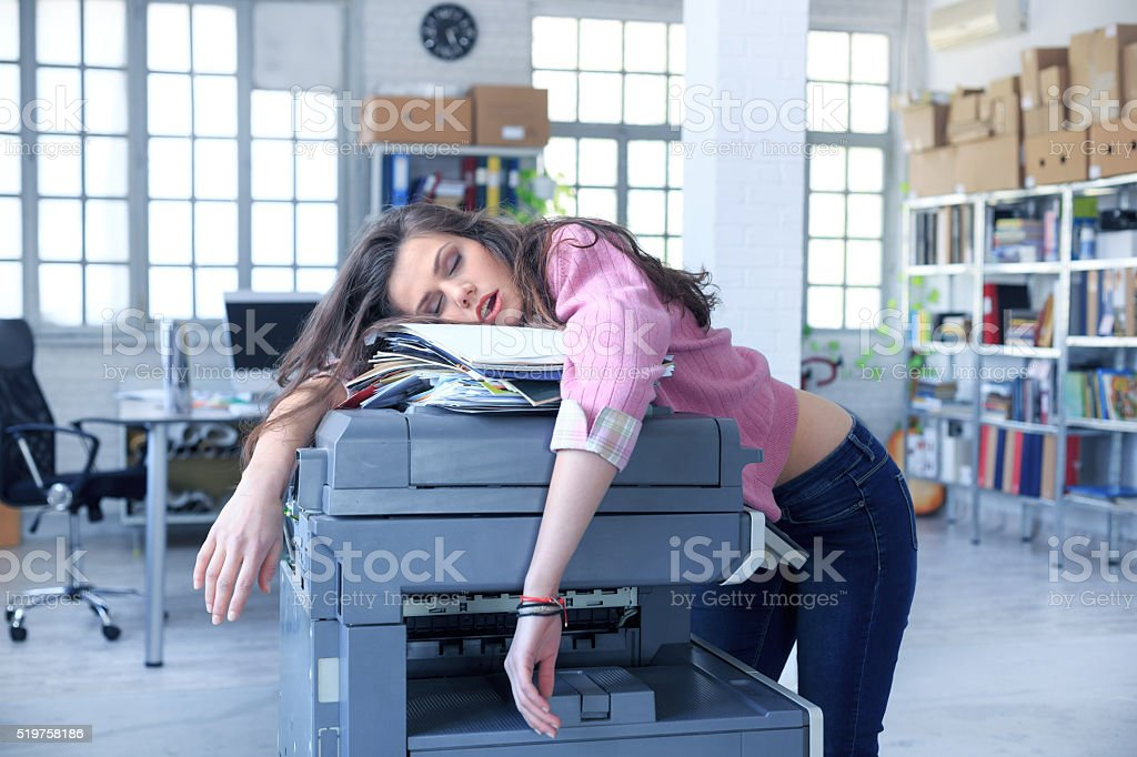 Tired assistant sleeping on a copy machine stock photo