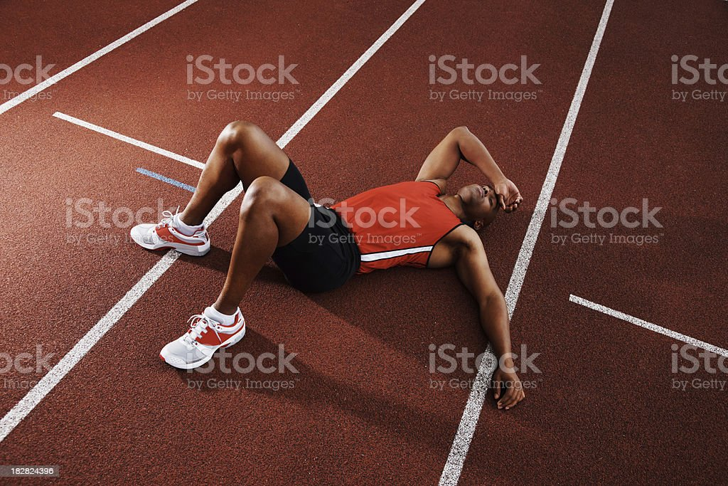 Tired athlete man lying on running track royalty-free stock photo