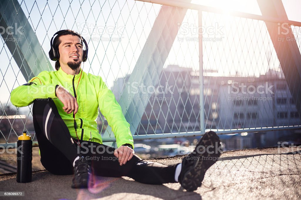 Tired athlete resting on the bridge after jogging royalty-free stock photo