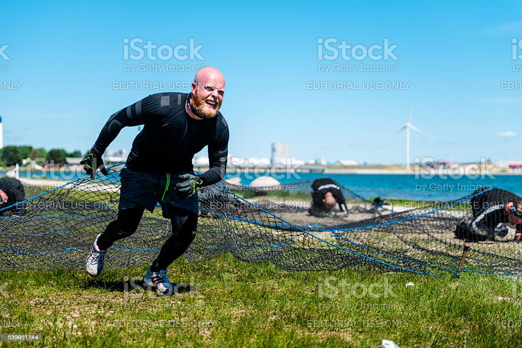 Tired athlete runs on an obstacle course stock photo