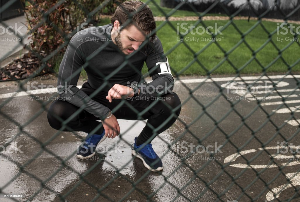 tired athletic man checking time on his watch after running on the rain stock photo