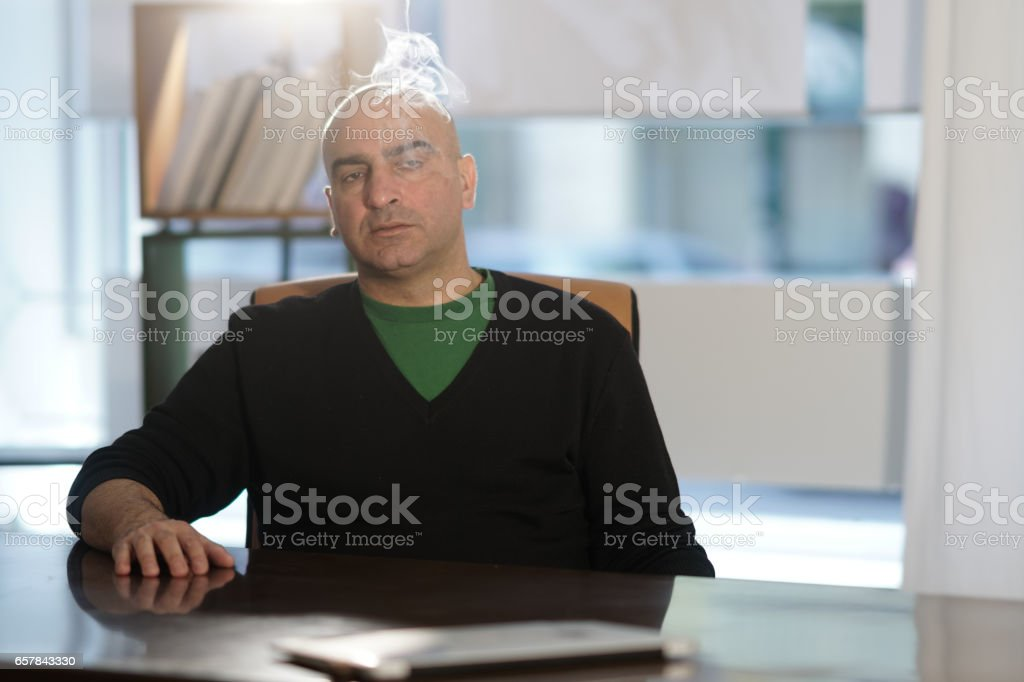 Tired bald headed office worker at desk