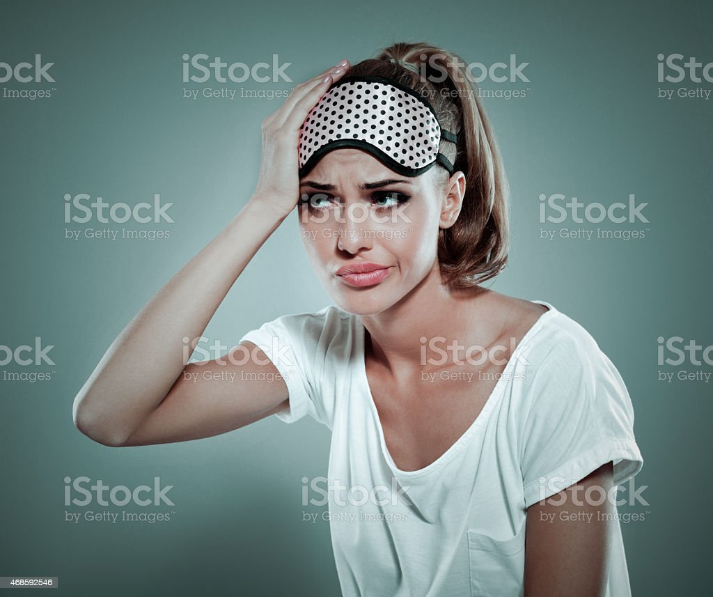 Tired blonde woman wearing sleeping mask on her forehead stock photo