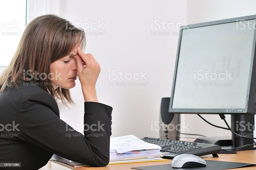 Tired business person with headache in work stock photo