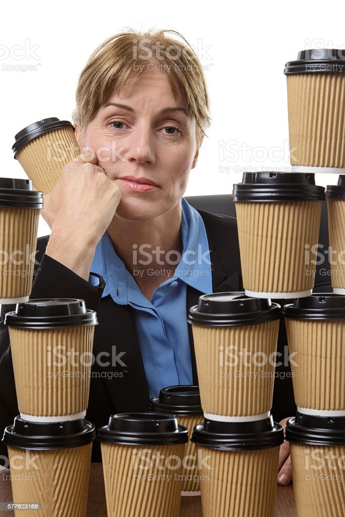 Tired business woman and disposable cups stock photo