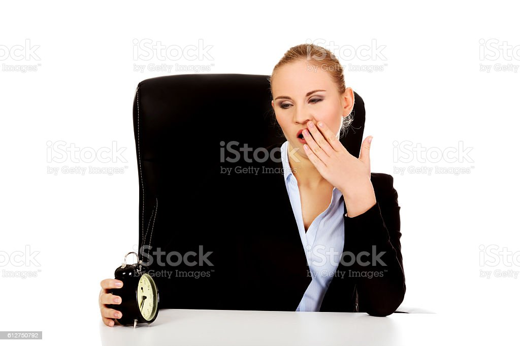 Tired business woman behind the desk with alarm clock stock photo