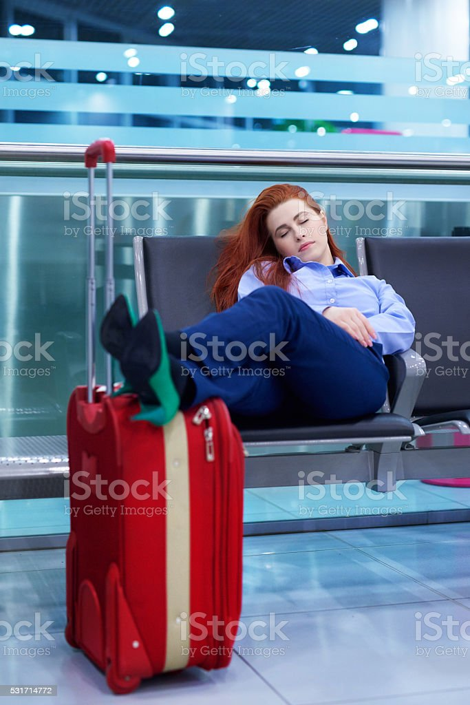 tired business woman in airport lounge stock photo