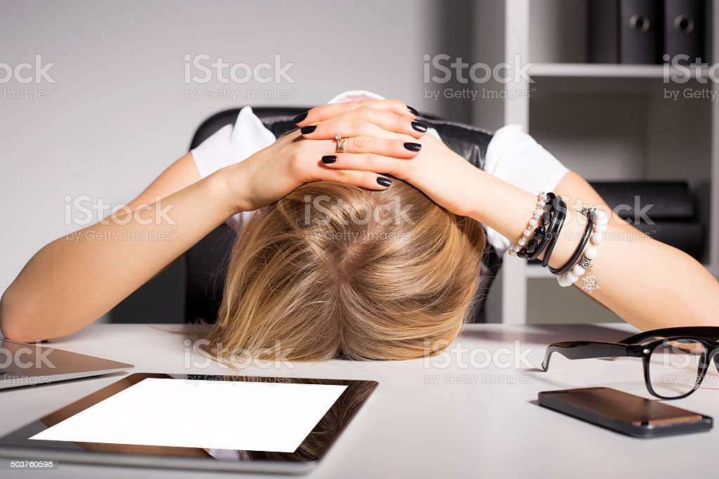 Tired business woman resting her head on desk stock photo