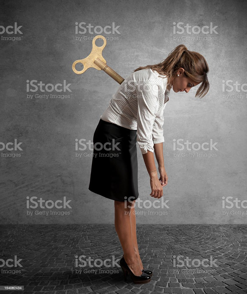 A tired business woman who has been stabbed in the back stock photo