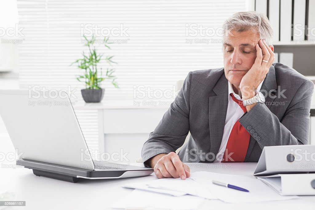 Tired businessman falling asleep at desk stock photo