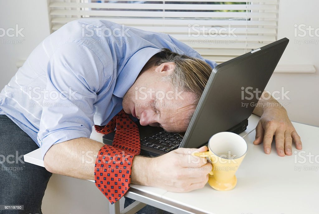 Tired businessman holding coffee cup asleep on his laptop stock photo