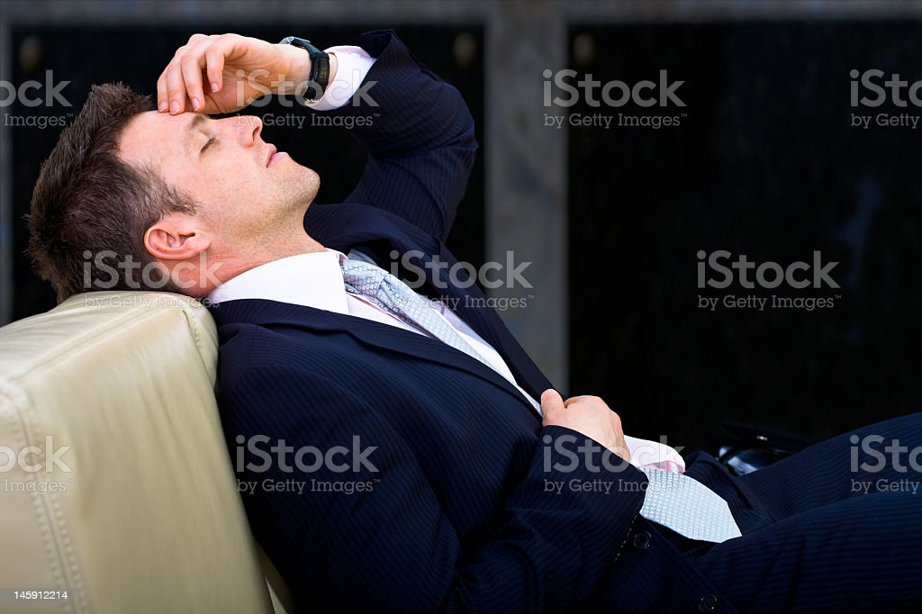 Tired businessman leaning back on a couch with eyes closed stock photo