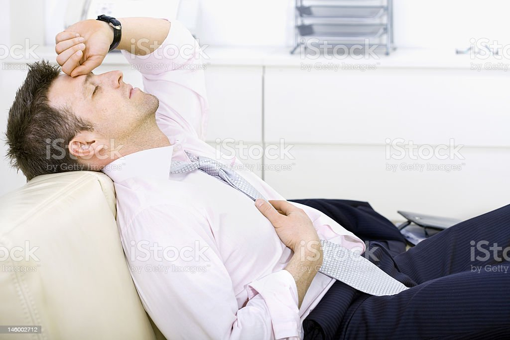 A tired businessman resting on a couch stock photo