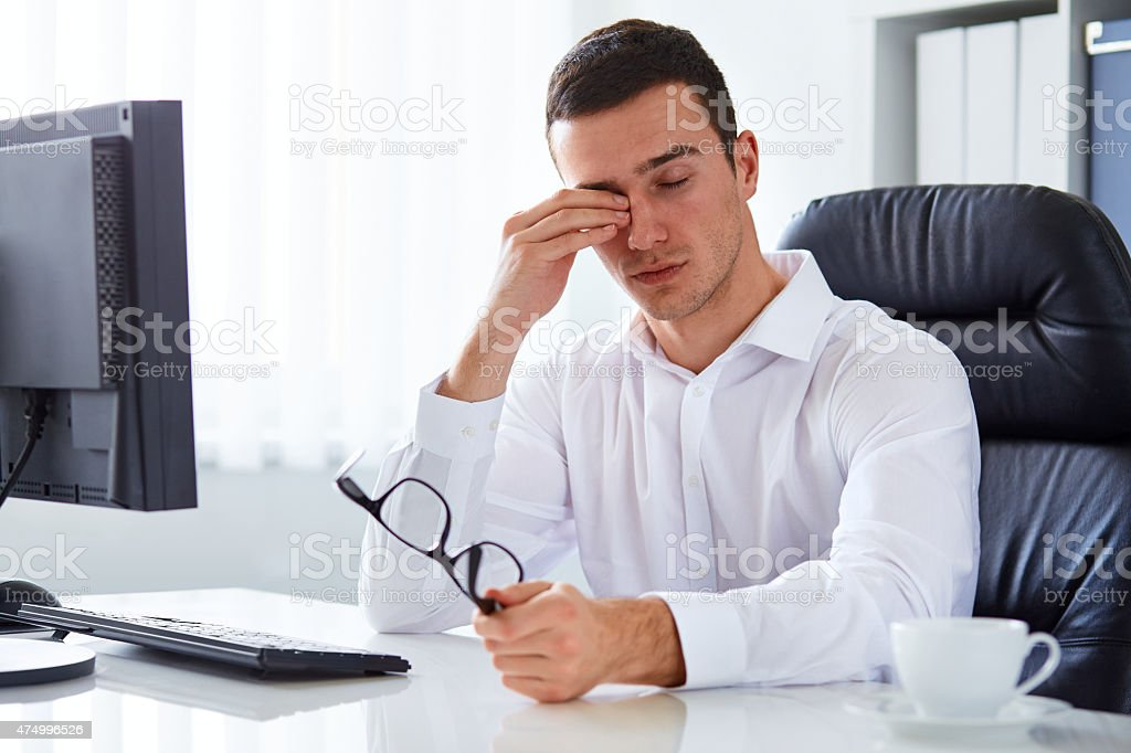 Tired businessman rubbing his eye stock photo