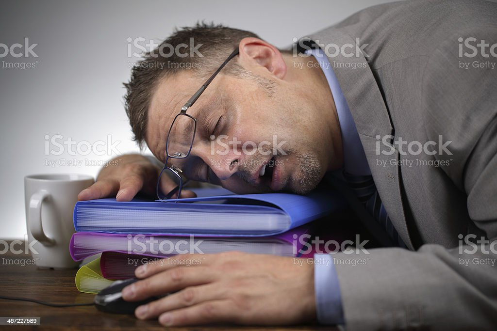 Tired businessman sleeping on files stock photo