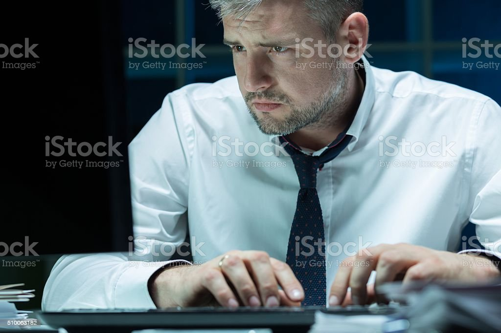 Tired businessman working at night stock photo