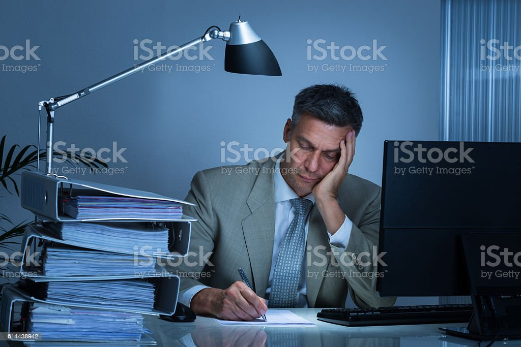Tired Businessman Writing On Document While Working Late stock photo