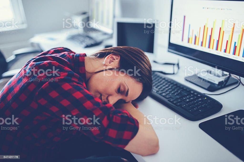 Tired businesswoman sleeping on the desk stock photo