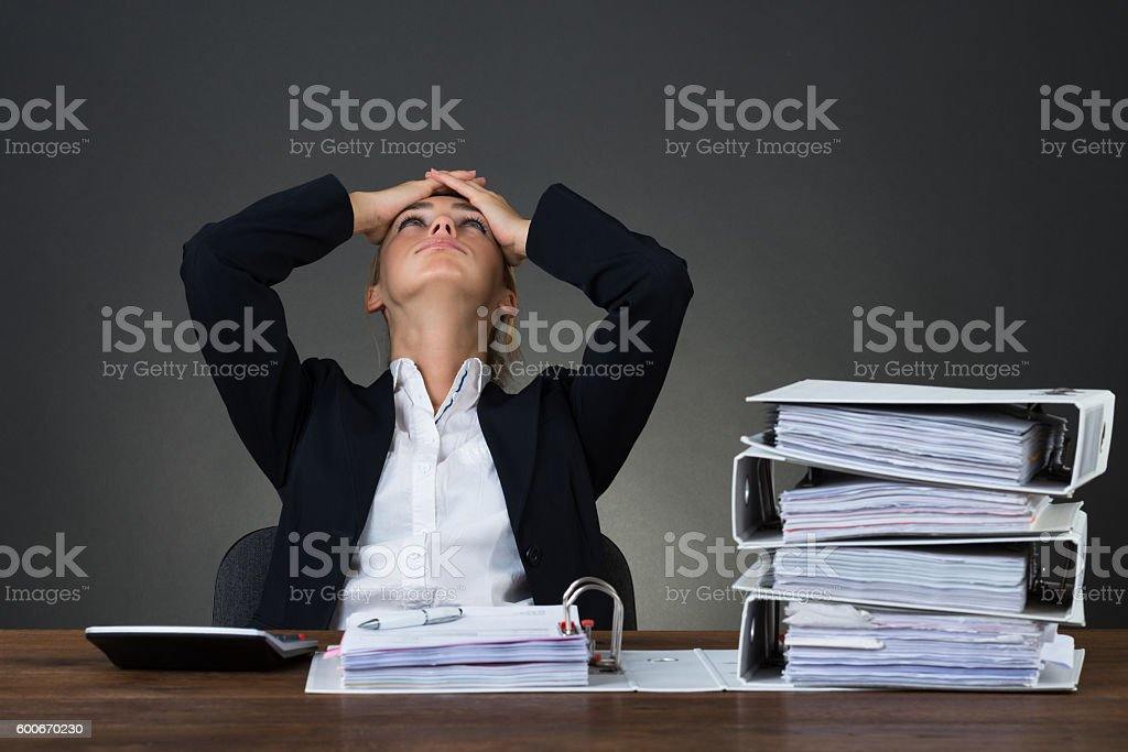 Tired Businesswoman With Hands On Head At Desk stock photo