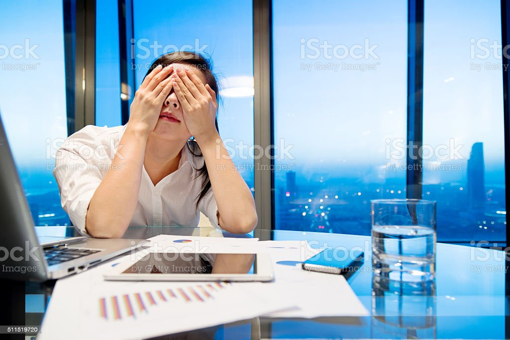 Tired businesswoman with laptop stock photo