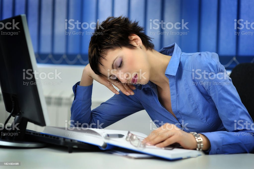 A tired businesswoman working in an office stock photo