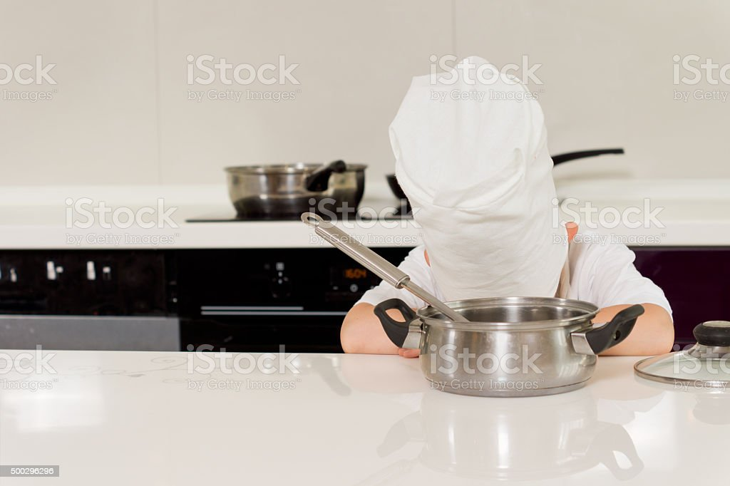 Tired chef laying head down on table stock photo