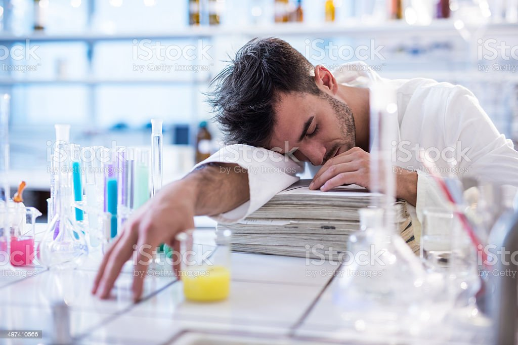 Tired chemist taking a nap in a laboratory. stock photo