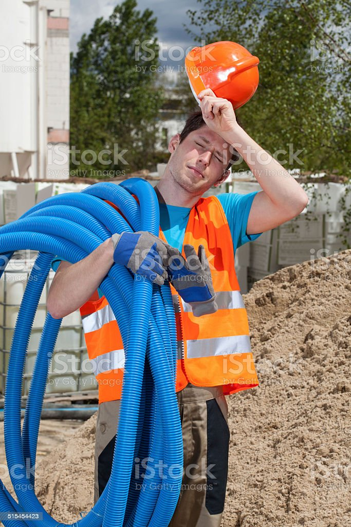Tired construction worker holding pipes stock photo
