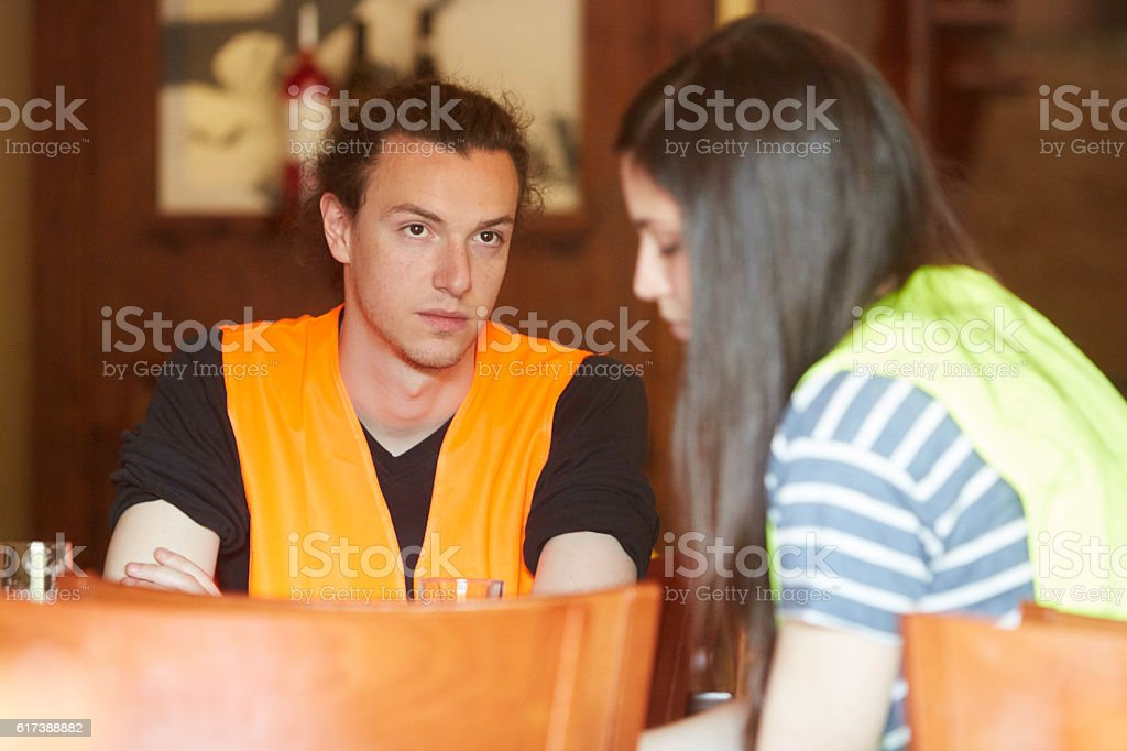 Tired construction worker sitting at restaurant table with female colleague stock photo