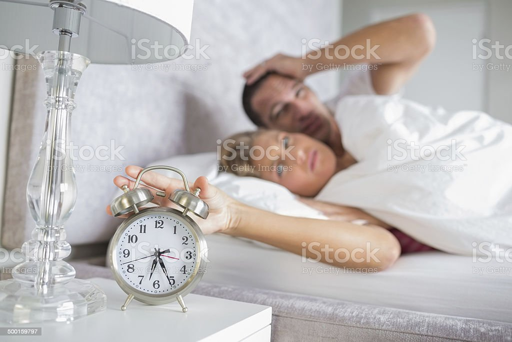 Tired couple looking at alarm clock in the morning stock photo