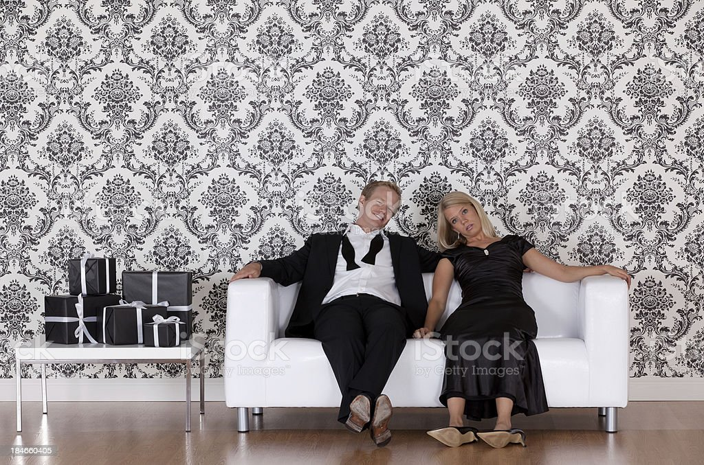 Tired couple sitting on couch after party royalty-free stock photo