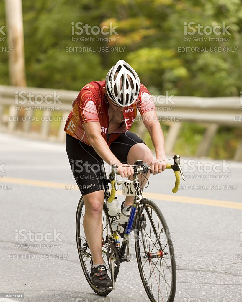 Tired Cyclist Struggles up a Mountain Slope, royalty-free stock photo
