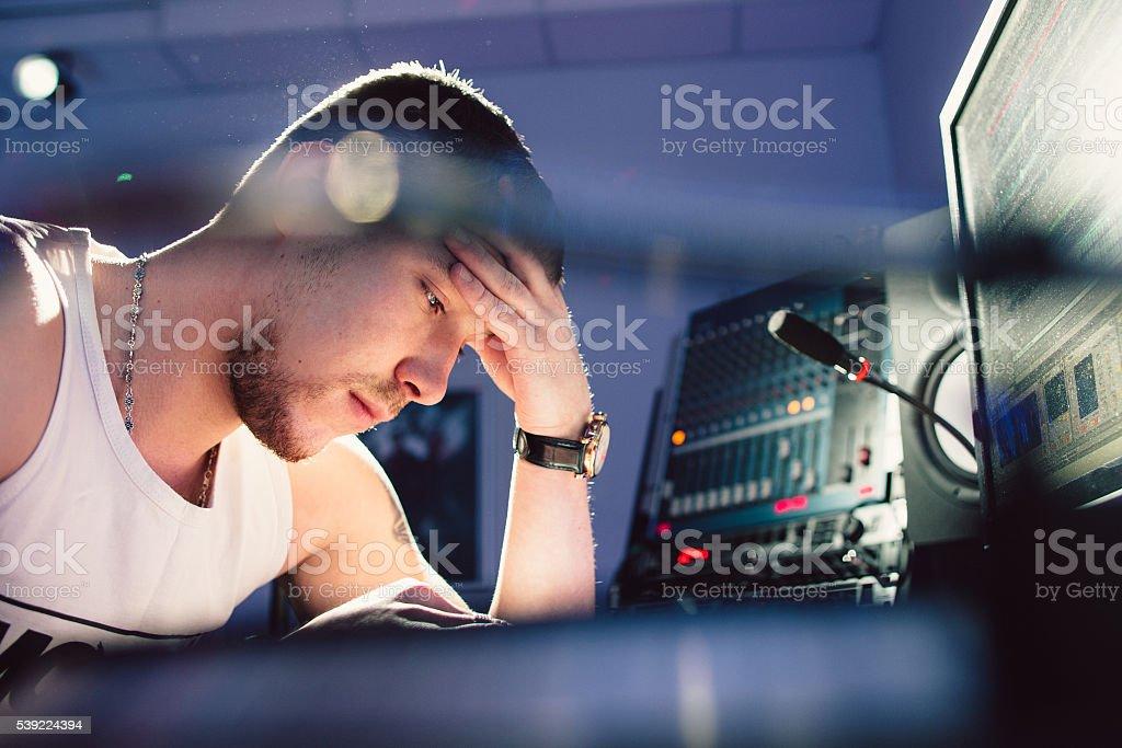 Tired dj sitting at studio close-up stock photo